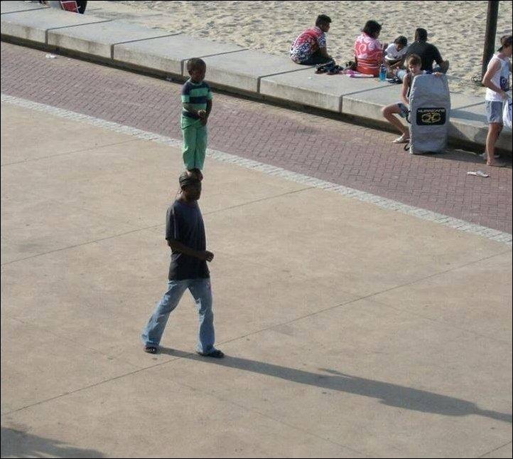 Мальчик стоит на голове отца