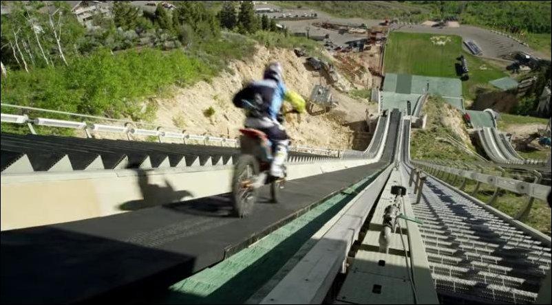 Прыжок на мотоцикле с трамплина для лыжников